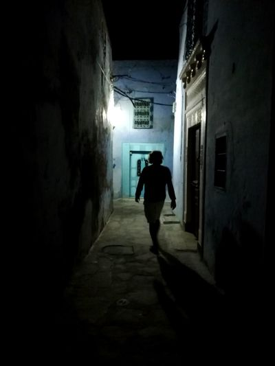 Rear view of silhouette man walking in alley amidst buildings
