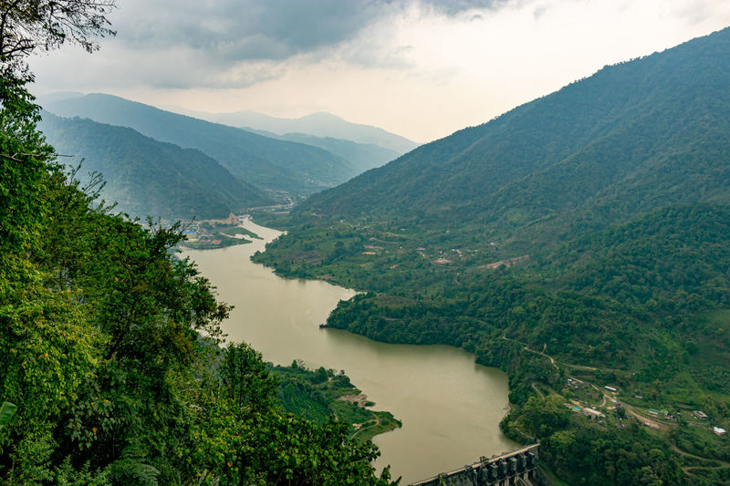 Mountain valley with cloudy sky and river leading at morning from flat angle