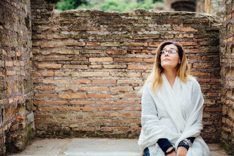 Young woman looking away while sitting against brick wall
