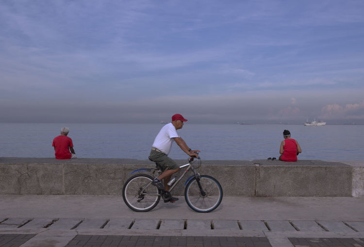 People sitting on retaining wall by sea against sky