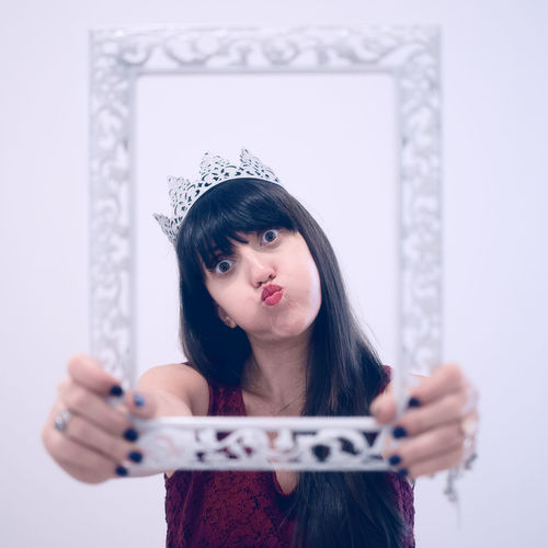 Portrait Of Young Woman Wearing Crown Holding Picture Frame While Standing Against White Background