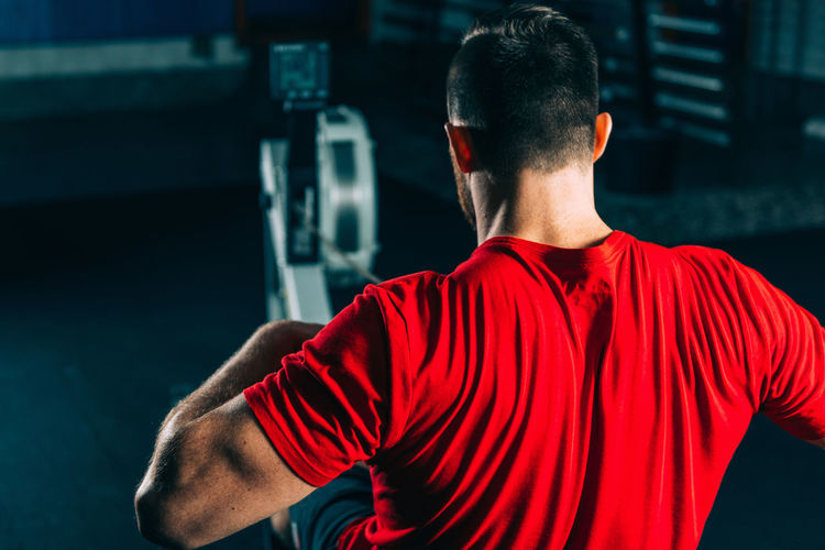 Rear View Of Male Athlete Exercising In Gym