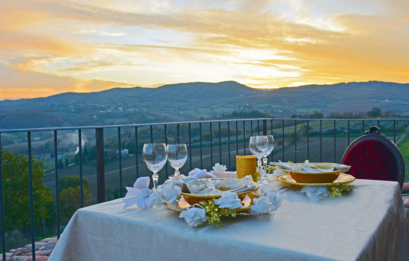Food on table at restaurant against sky during sunset