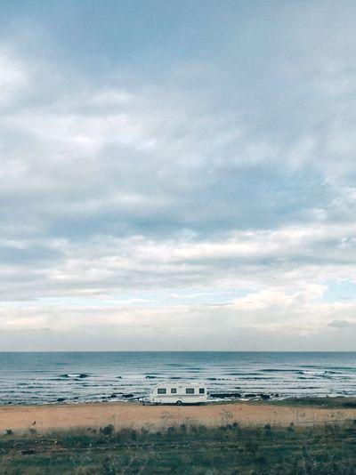 Camper van on shore at beach against cloudy sky
