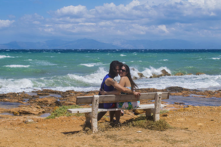 Portrait Of Two Woman Sitting On Bench At Beach Against Sky