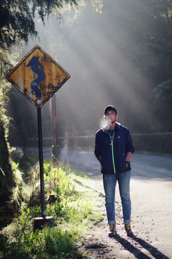 Full length of young man standing by road