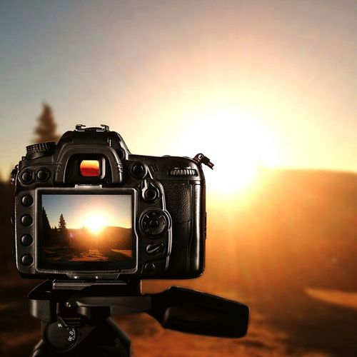 Close-up of silhouette camera against sky during sunset