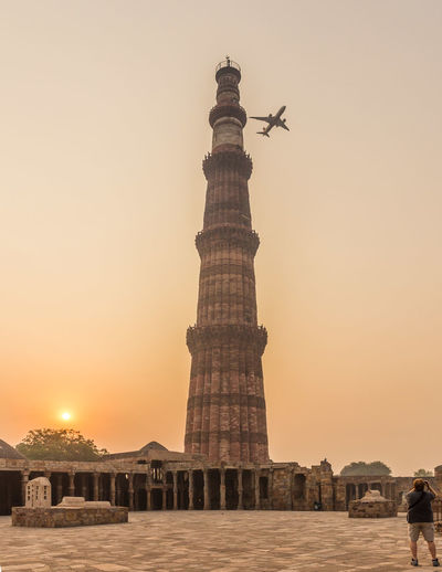 Low angle view of airplane in flight over tower