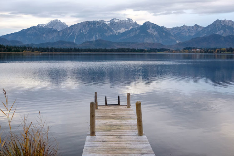Wooden posts in lake by mountains against sky