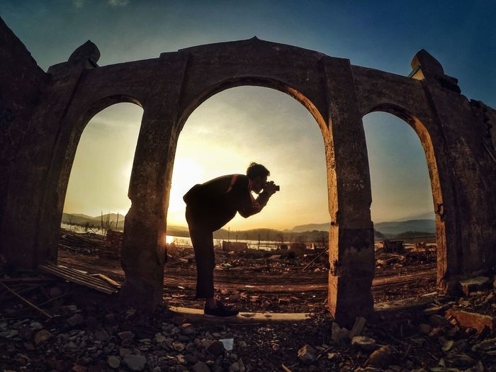 Man photographing at old ruins during sunset
