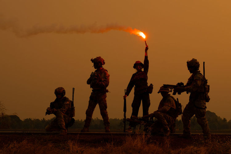 Armed forces standing on railroad track against sky during sunset