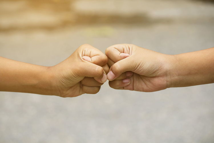 Cropped image of hands fist bumping outdoors