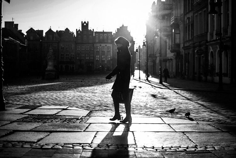 Side view of woman walking on cobbled street