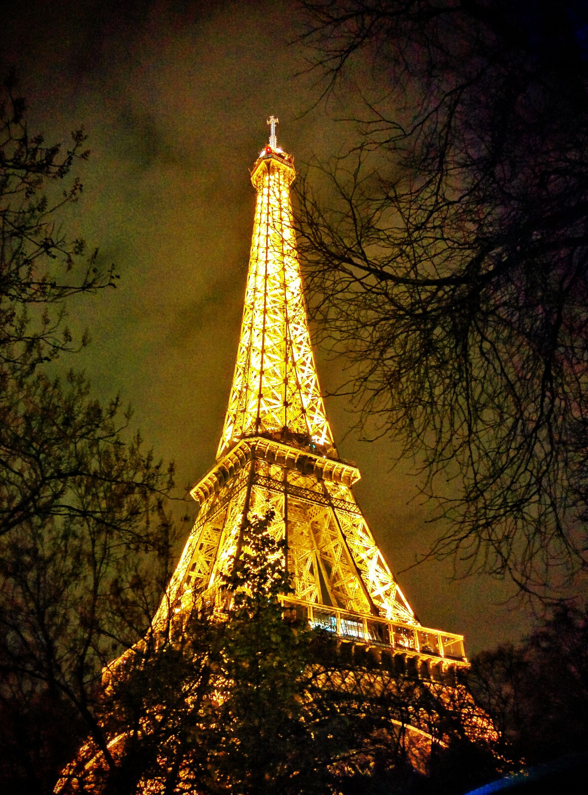 architecture, built structure, famous place, eiffel tower, tower, international landmark, travel destinations, tall - high, tourism, capital cities, travel, building exterior, low angle view, tree, culture, city, sky, spire, illuminated, architectural feature
