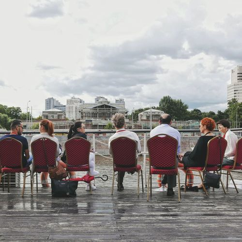 People sitting on table in city against sky