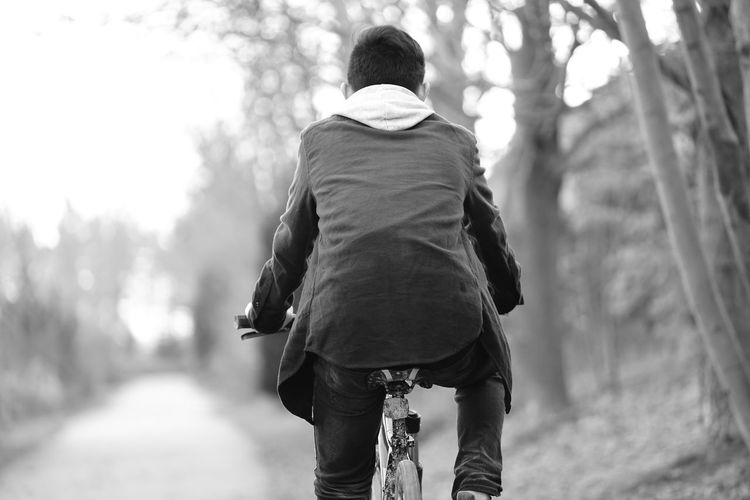 Rear view of teenage boy cycling on road
