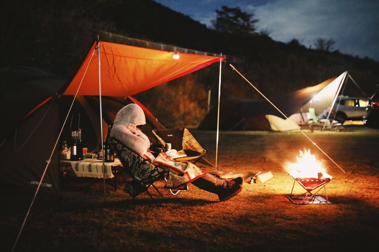 Woman sitting by fire pit in tent against sky at night