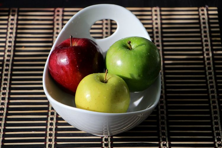 Fresh wet apples in bowl on table