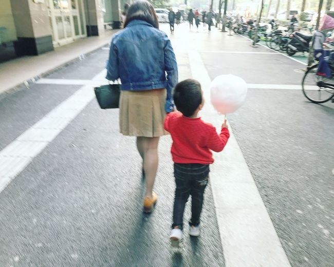 Rear view of mother and daughter walking on street