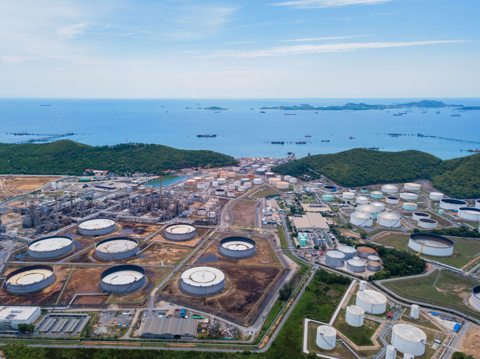 Aerial view of petrochemical oil refinery and sea in industrial engineering concept in Laem Chabang, Chonburi province, Thailand. Oil and gas tanks industry. Modern factory. Top view. Swimming Pool Outdoors No People Scenics - Nature Building Built Structure Horizon Over Water Day Building Exterior Aerial View Cloud - Sky Horizon Nature High Angle View Water Sky Steam Tube Background Chemistry Pollution Chemical Port Petrol Architecture Urban Smoke Construction Business Storage Tank Pattern Transportation Hill Cityscape Town Tourism Travel City Station Petroleum Pipe Fuel Engineering Industrial Power Environment Equipment Technology Plant Chonburi Production Industry Gasoline Aerial Factory Thailand Top Gas Oil Energy Sea Blue Petrochemical Refinery Buildings