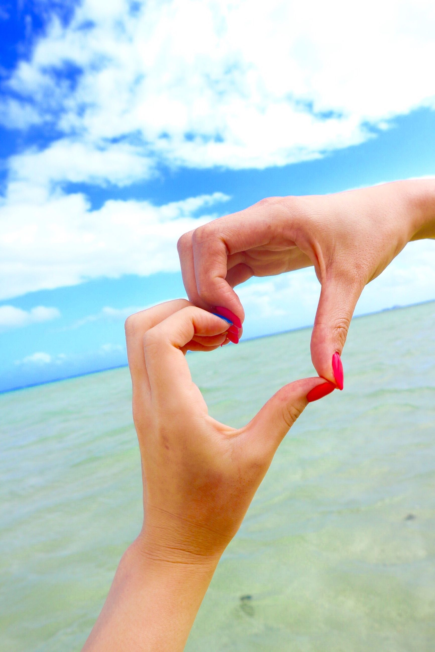 human hand, human body part, sea, sky, beach, human finger, cloud - sky, horizon over water, outdoors, vacations, one person, close-up, day, real people, beauty in nature, adults only, nature, water, freshness, people, adult