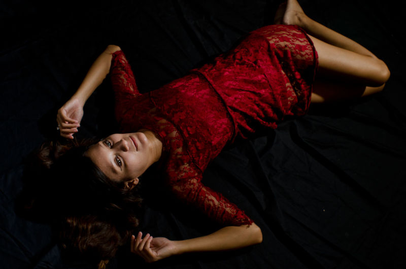 High angle view of beautiful woman wearing red dress while lying on bed at home