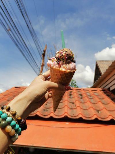 Hand holding ice cream against sky