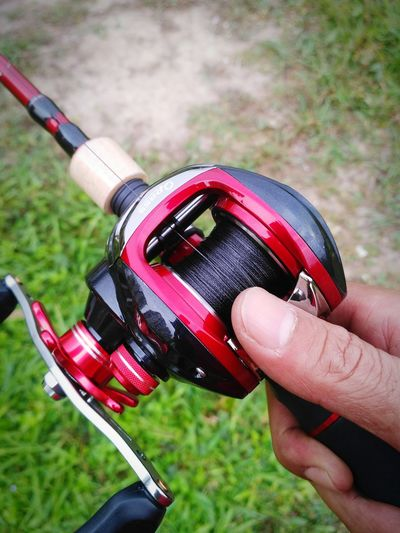 Hand holding bait casting reel. Casting Reel Fishing Gear Angler Fisherman Ball Bearings Fresh Water Fish Fresh Water Lake Salt Water Fish Salt Water Fishing Lures Minnow Popper Casting Rod Fishing Activity Spool Magnesium Alloy Adventure Activity Bait Cast Reel Cork Handle Rod Close-up Day Outdoors Grass Adult
