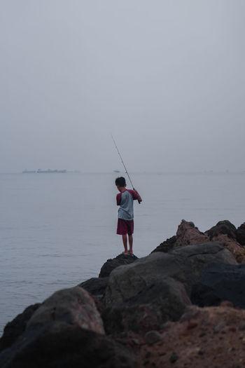 Rear view of boy fishing in sea against sky