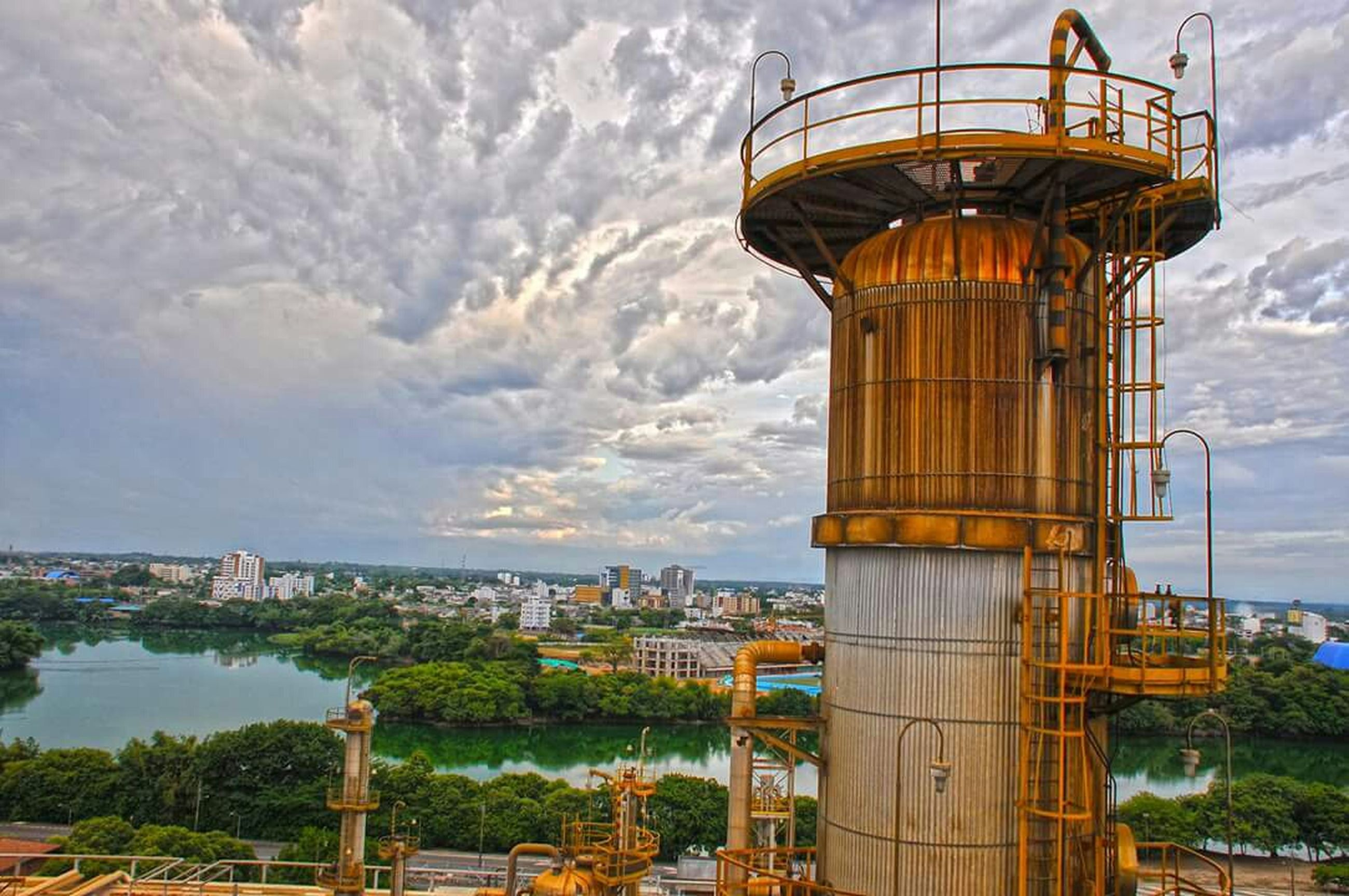 architecture, built structure, sky, building exterior, cloud - sky, cloudy, cloud, city, tower, outdoors, tree, day, low angle view, travel destinations, no people, connection, incidental people, river, railing, residential building