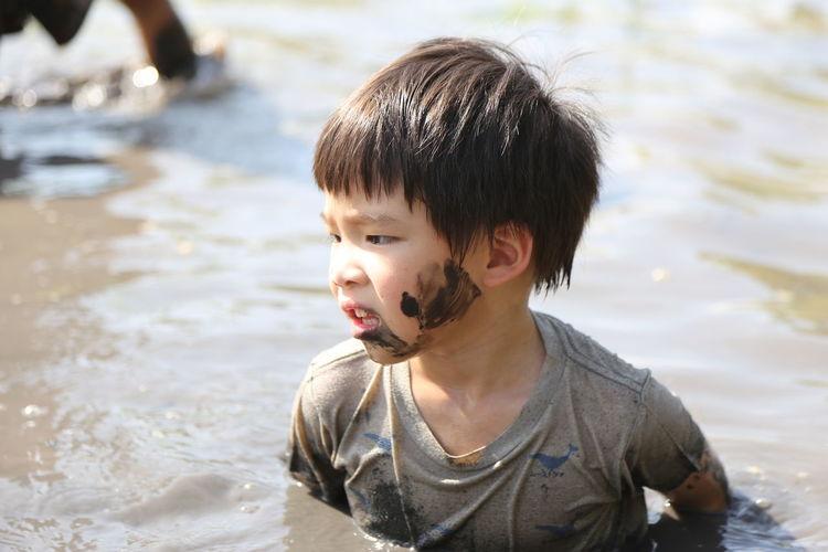 Messy boy in muddy water
