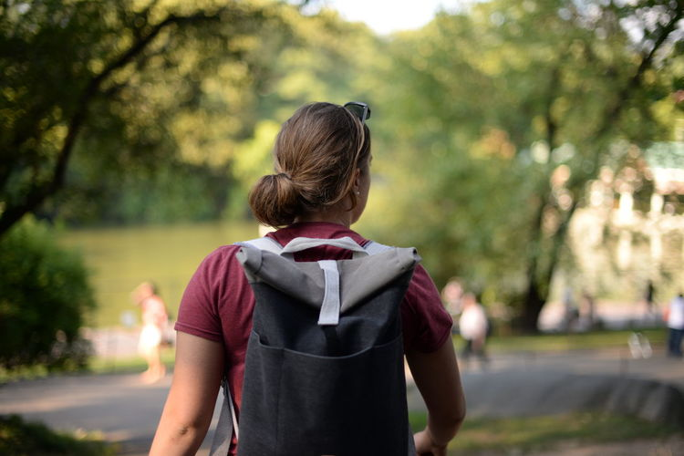 Rear view of girl standing against trees