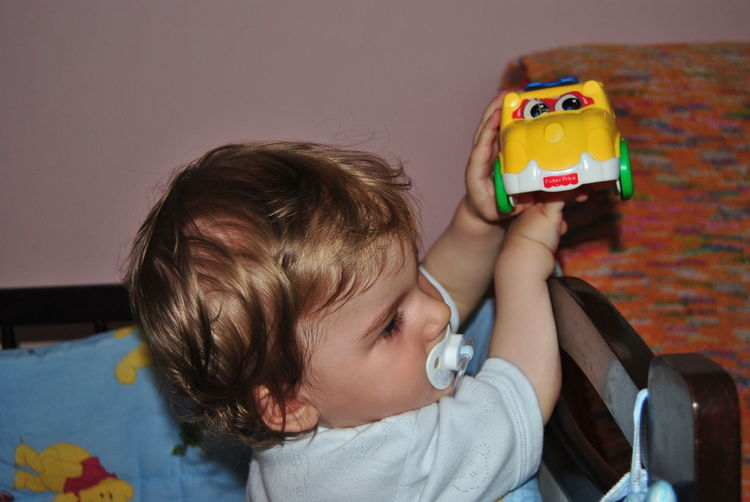 Cute baby boy sucking pacifier while playing with toy car at home