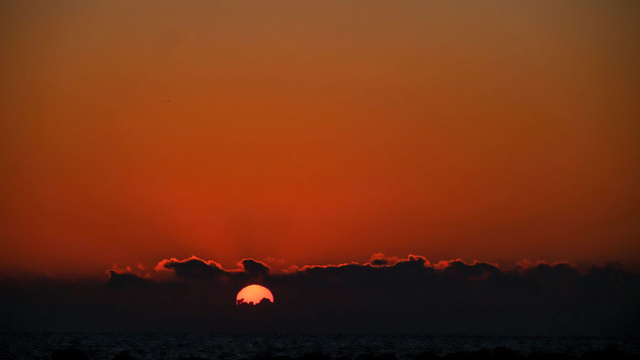 Silhouette mountain against orange sky