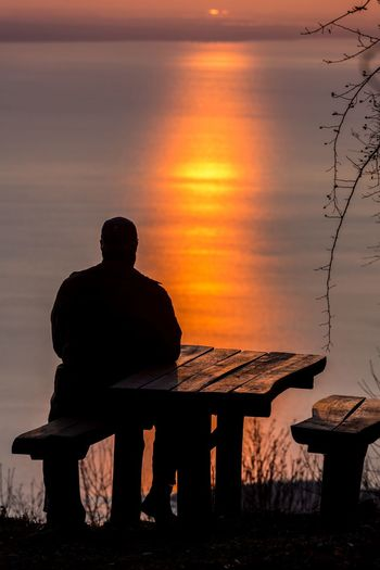 Rear view of silhouette man sitting on seat against sky during sunset
