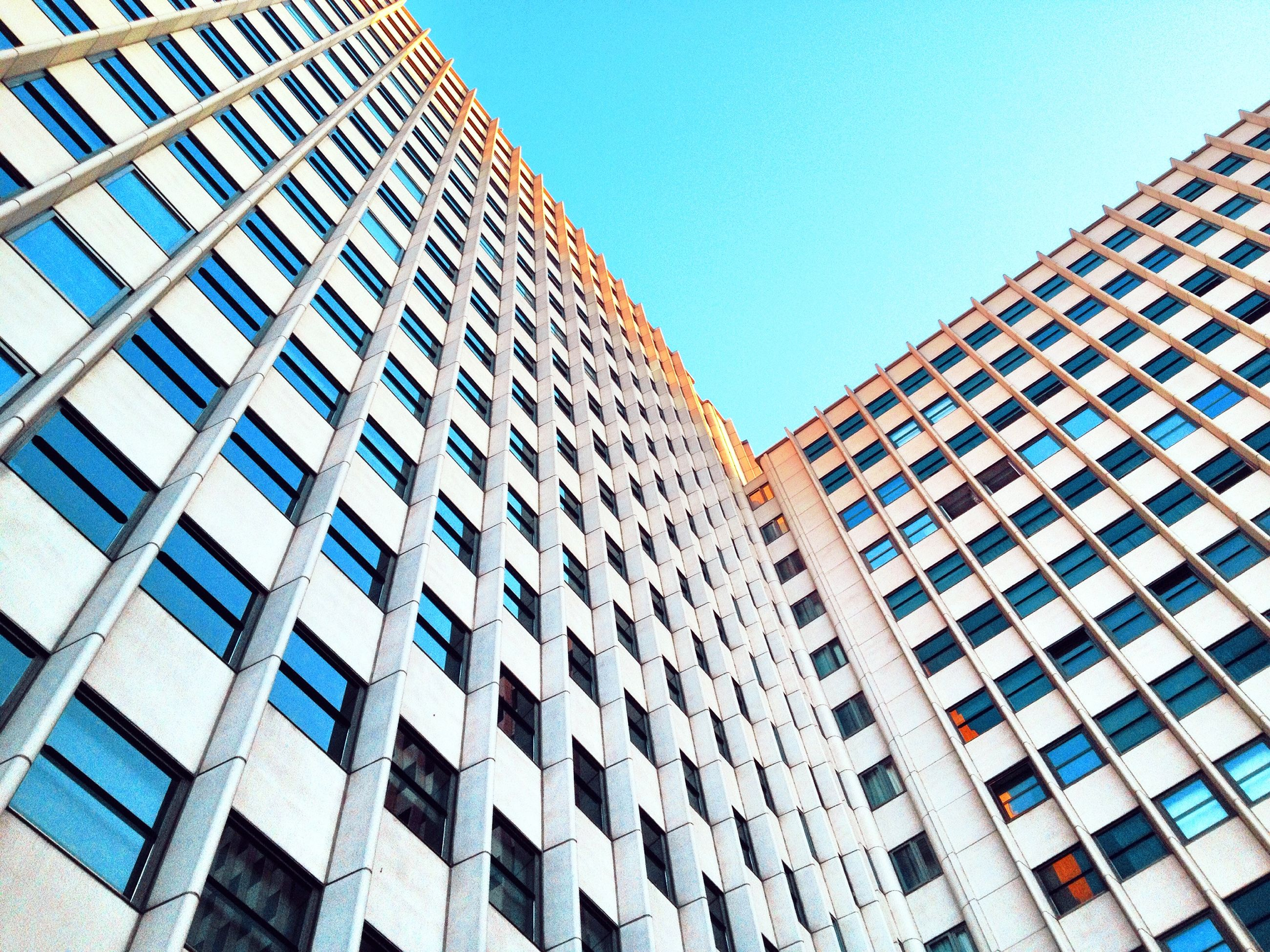 building exterior, architecture, built structure, low angle view, modern, city, office building, window, building, clear sky, skyscraper, tall - high, glass - material, tower, reflection, day, sky, repetition, no people, outdoors