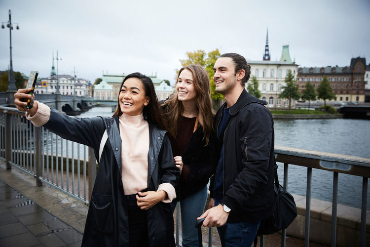 Friends standing on railing by river in city