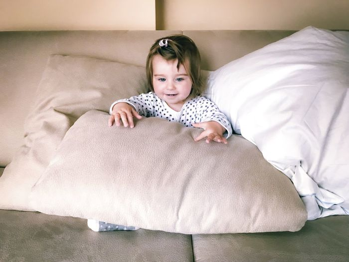 Full length of cute baby lying on bed at home