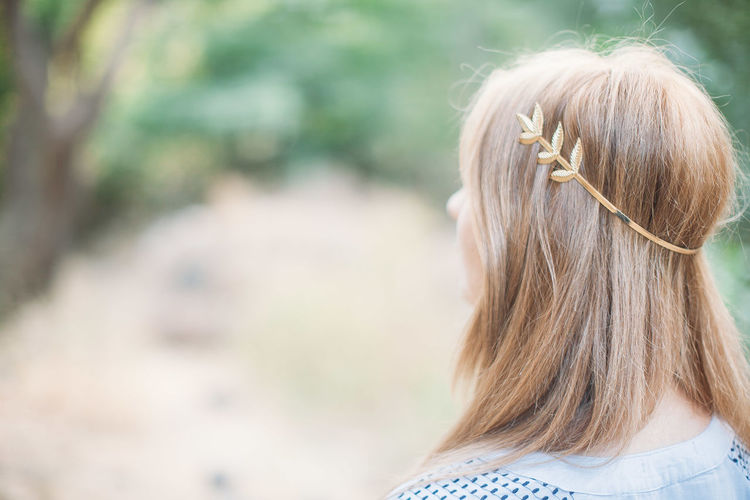 Rear view of woman wearing brooch in long blond hair at forest