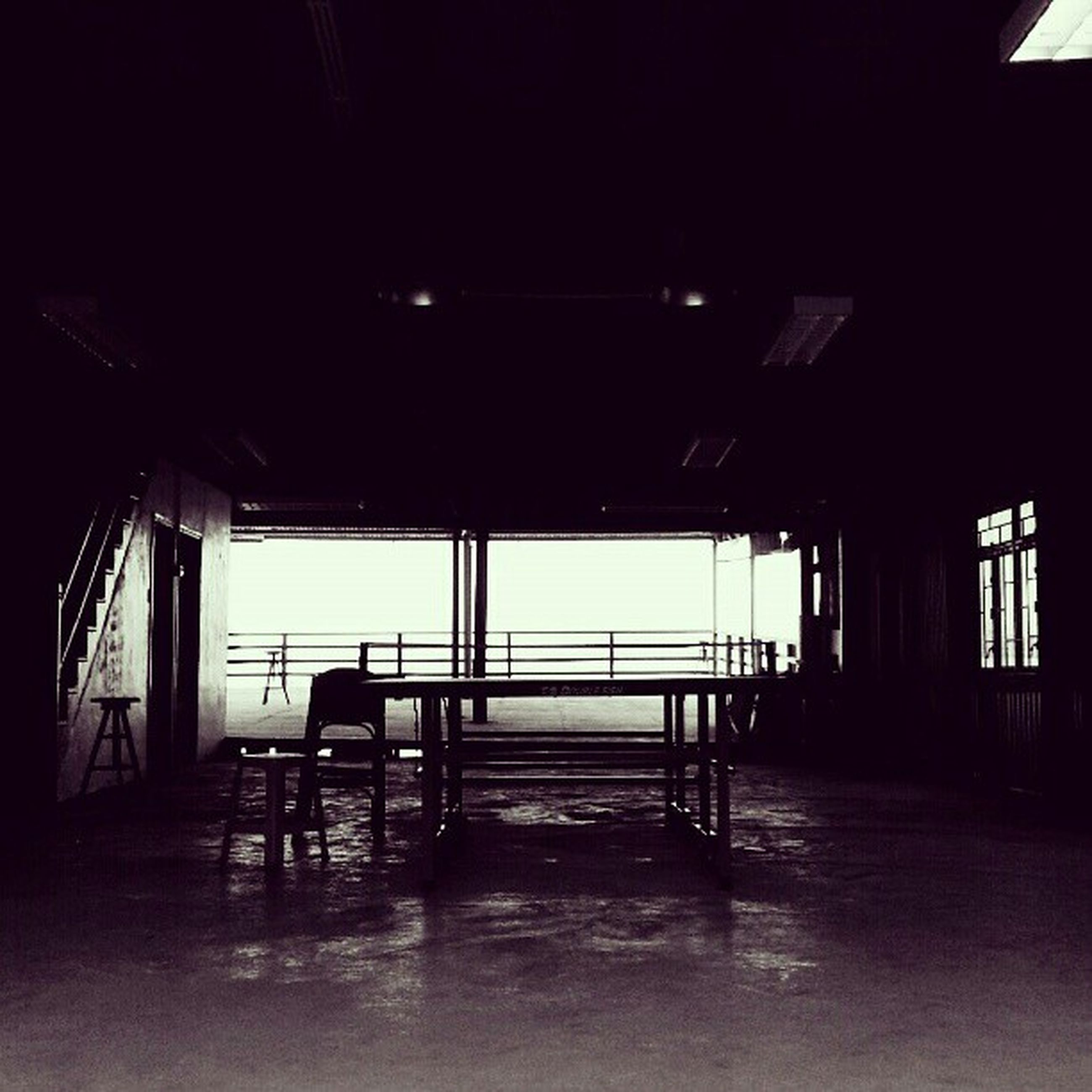indoors, architecture, built structure, window, empty, flooring, absence, chair, sunlight, glass - material, house, door, corridor, illuminated, dark, interior, building exterior, reflection, table, ceiling