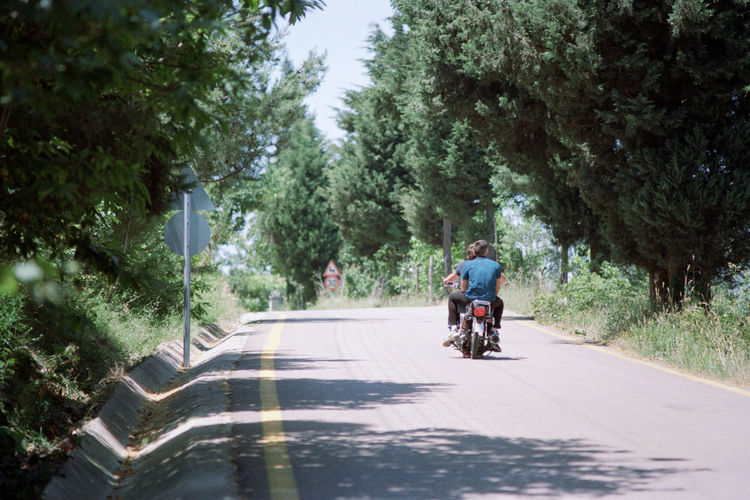 Rear view of men riding motorcycle on road