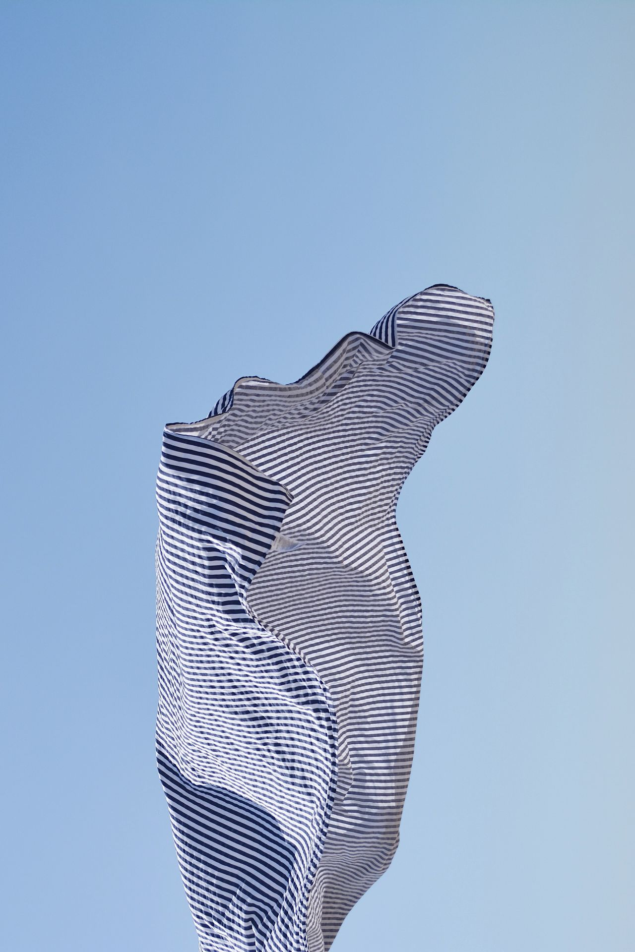 Low angle view of fabric against clear blue sky
