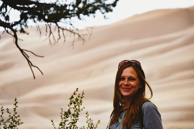 Portrait of smiling woman against sand dune