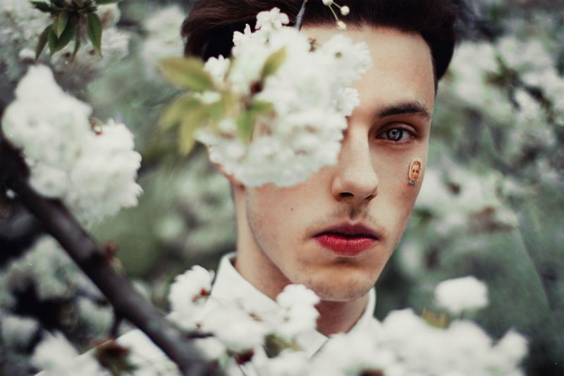 Close-up portrait of serious young man with white flowers in foreground