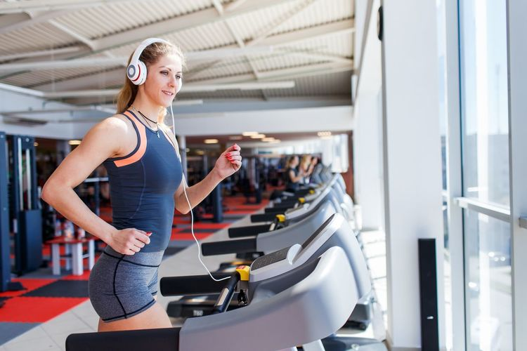 Young woman running on treadmill