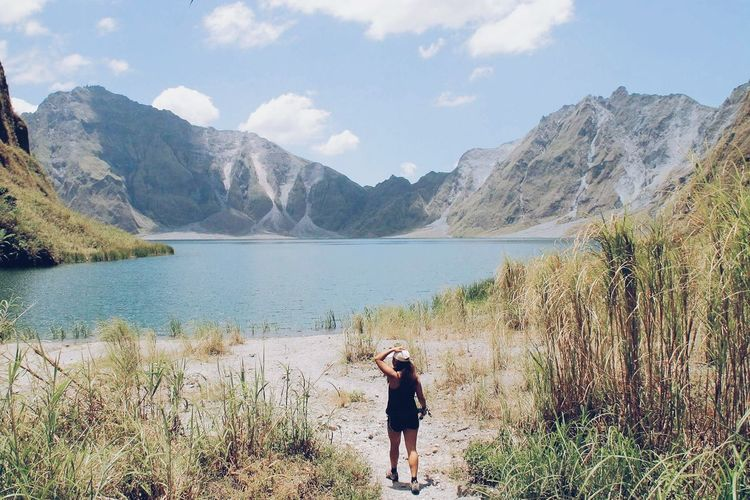Full length of young woman walking by lake against mountains