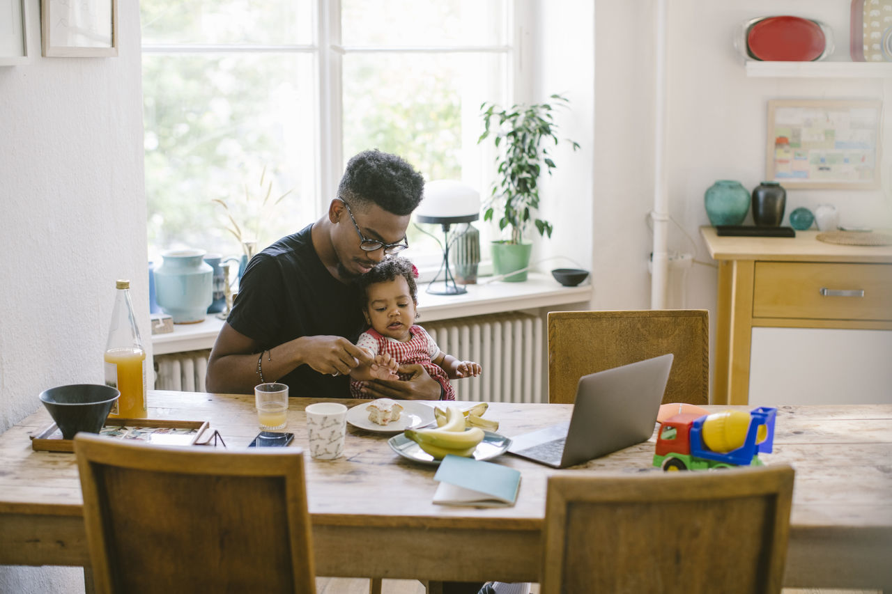 Young man playing with daughter while sitting at table in house