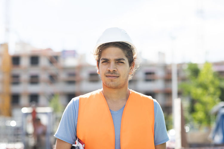 Portrait of young man standing against city