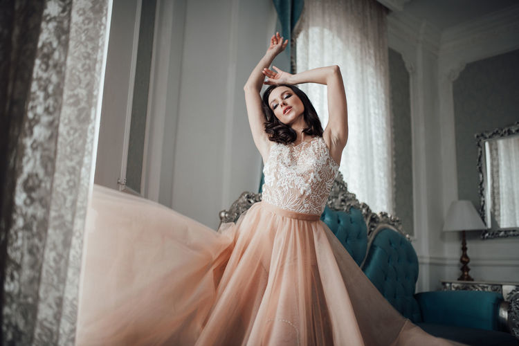 Woman wearing bridal dress standing at home