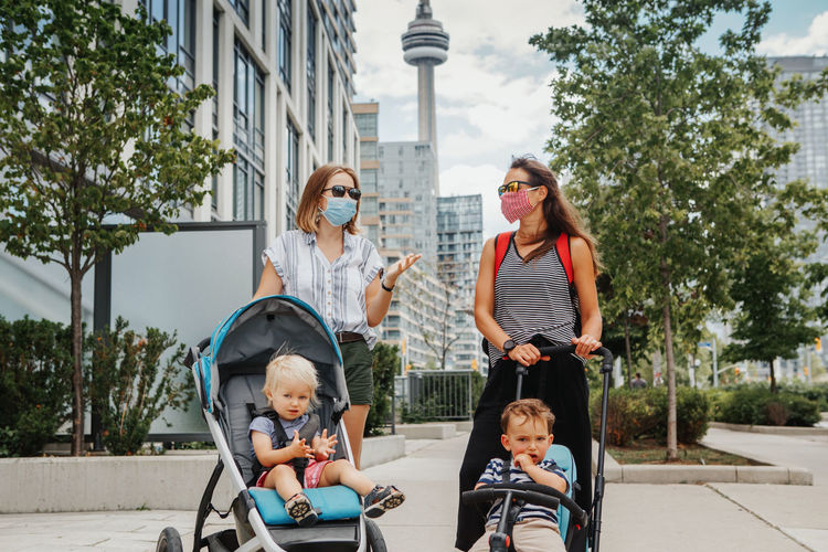 Two mothers walking with kids in strollers. social distance covid-19 coronavirus. new normal